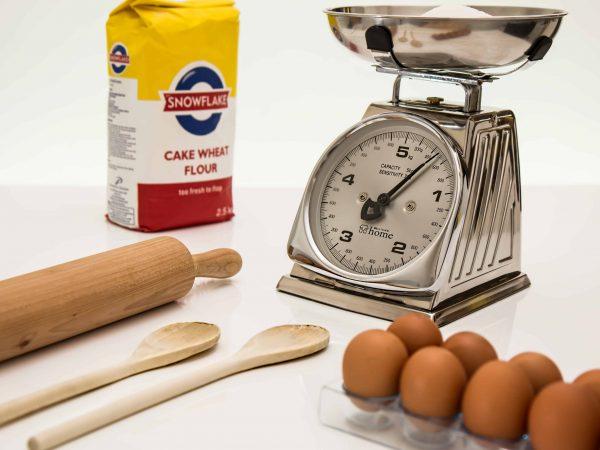 Imagem mostra uma balança de cozinha mecânica ao lado de um saco de farinha de trigo, uma caixa de ovos e utensílios de cozinha.