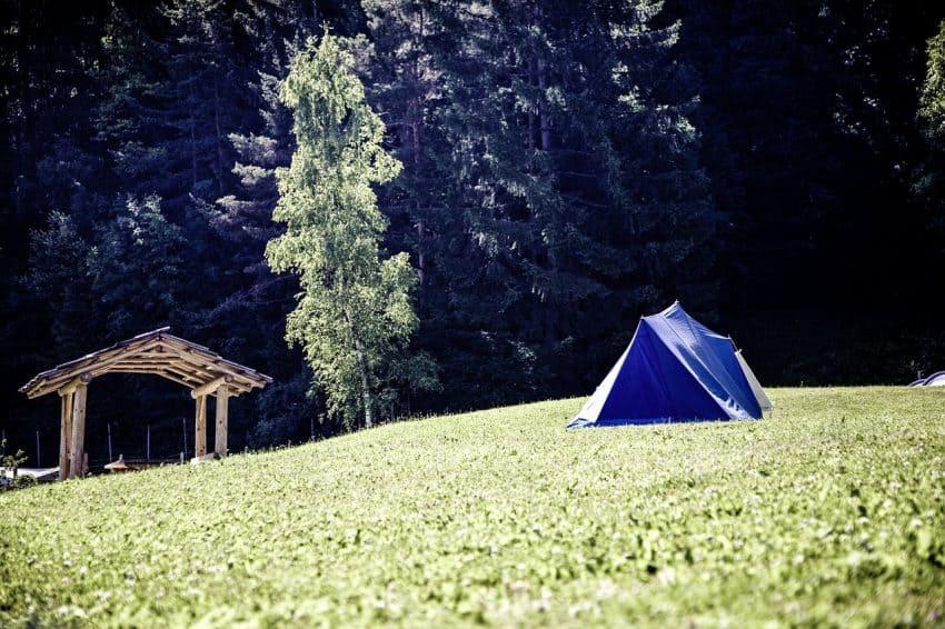 Imagem uma barraca triangular, modelo conhecido como canadense, armada em um gramado em meio à natureza.