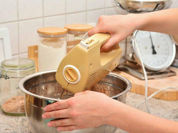 Foto de uma pessoa batendo alguma receita, utilizando a parte superior de uma batedeira de mão e uma tigela. Ao fundo, uma cozinha com potes de grãos.