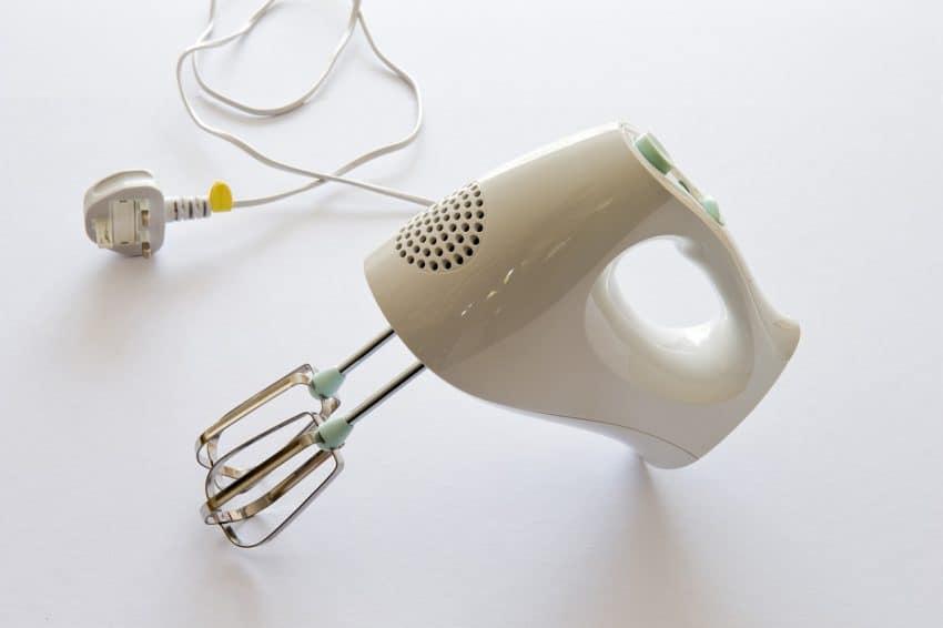 Foto de uma batedeira de mão branca, com fio desligado da tomada.