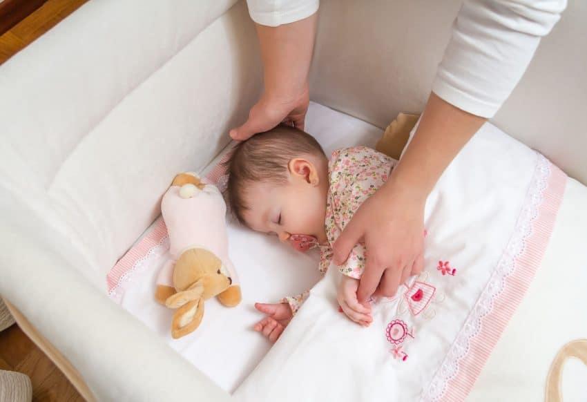 Berço com protetores acolchoados laterais, com bebê dormindo coberto por lençol, e as mãos da mãe segurando-o, com um ursinho de pelúcia ao lado.