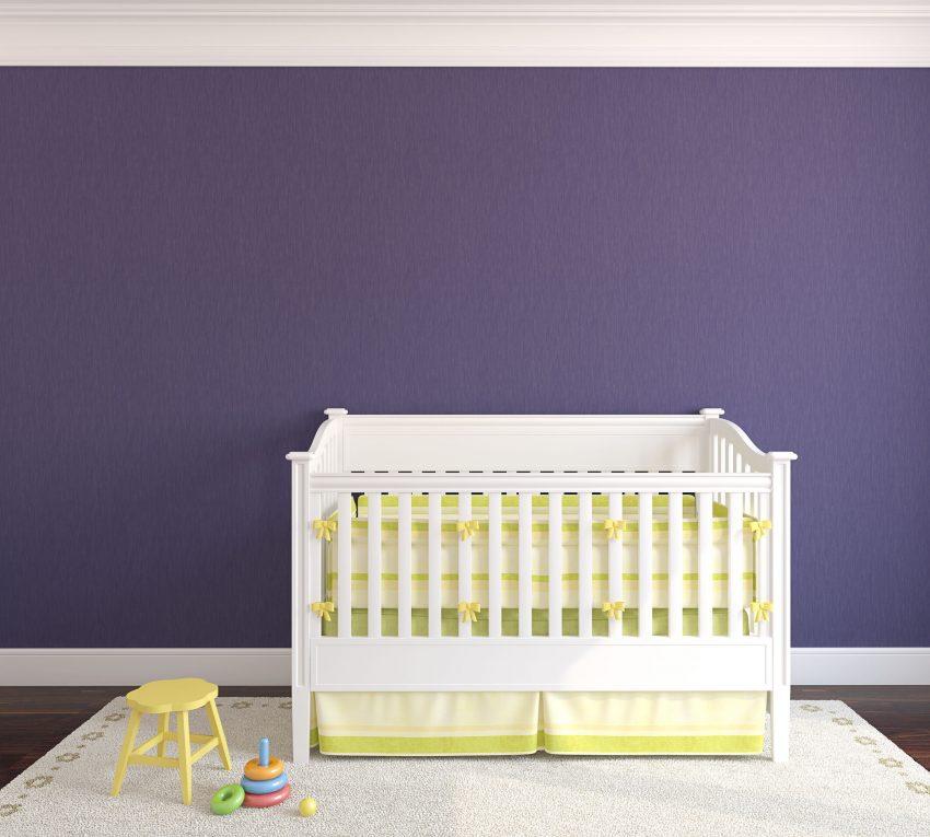 Quarto de bebê com parede azul escuro, tapete branco, banco de criança amarelo e berço branco com protetores de grade finos na cor amarelo.