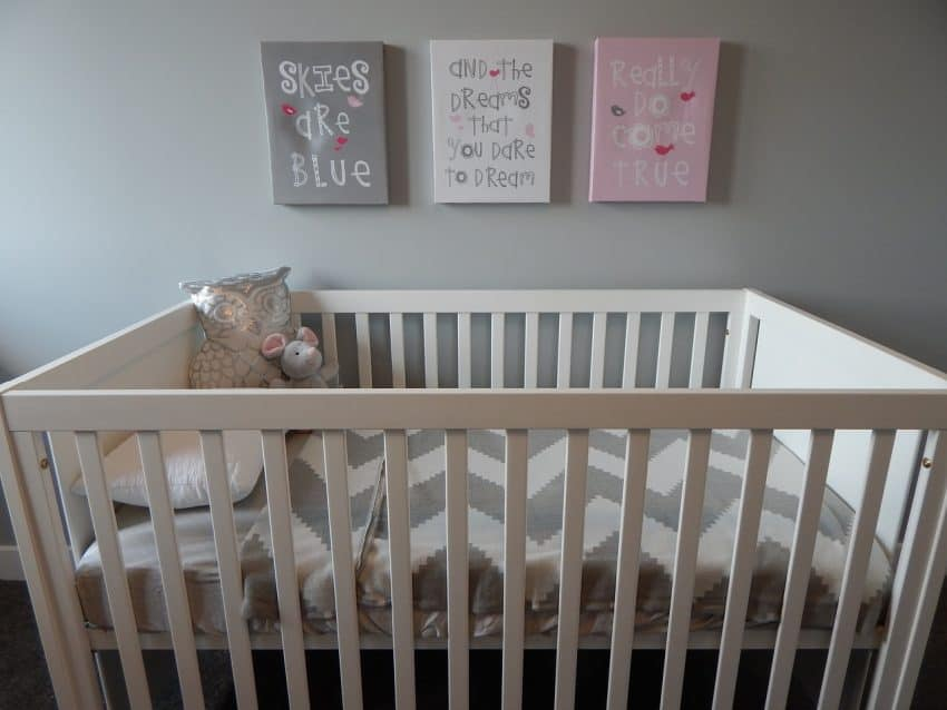 Quarto de bebê em tons de branco e cinza, com berço em destaque, apenas com lençol e ursinho de pelúcia, e quadros na parede.