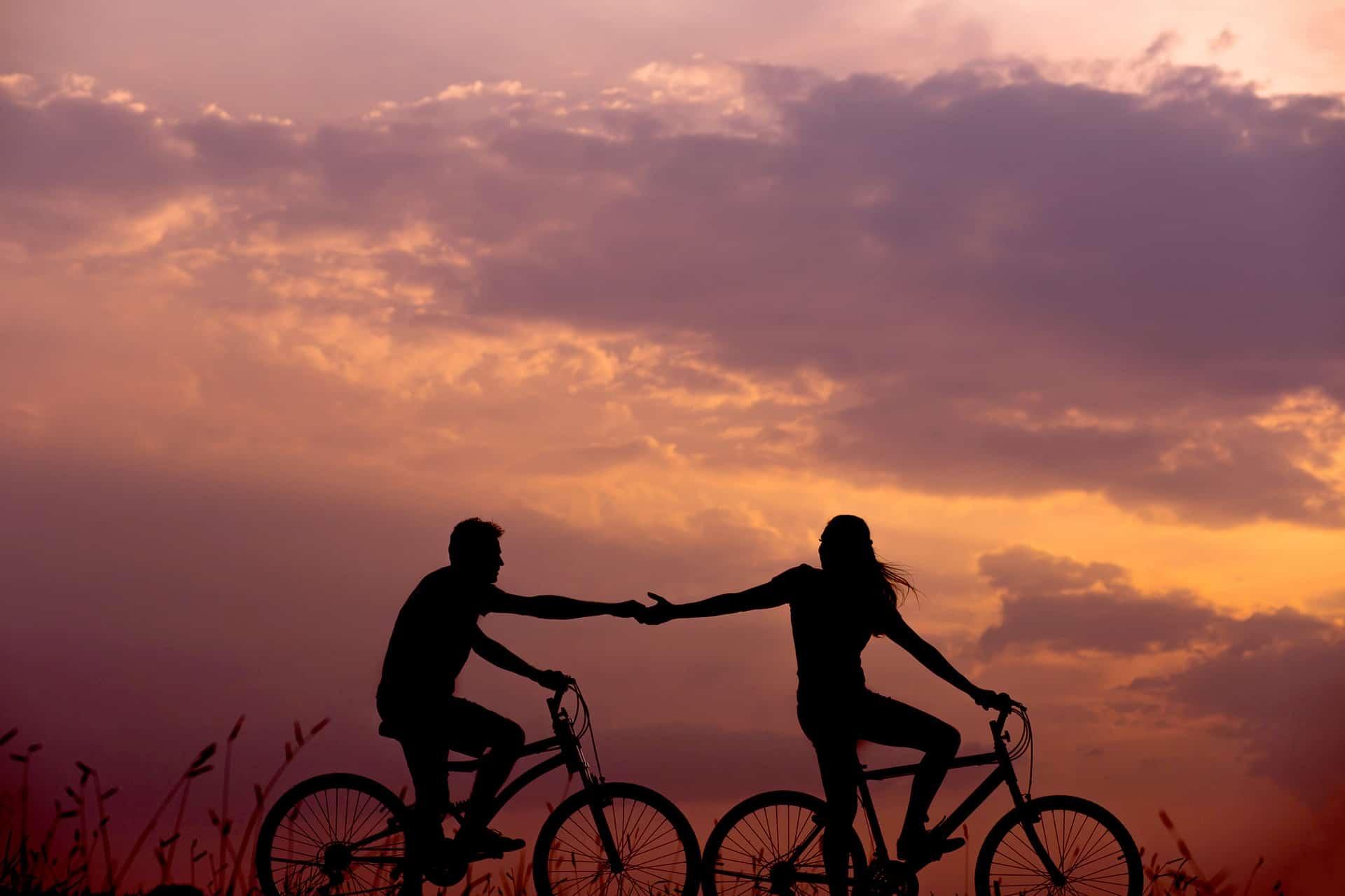 Casal sobre duas bicicletas, dão as mãos enquanto passeiam por uma bela paisagem rural.