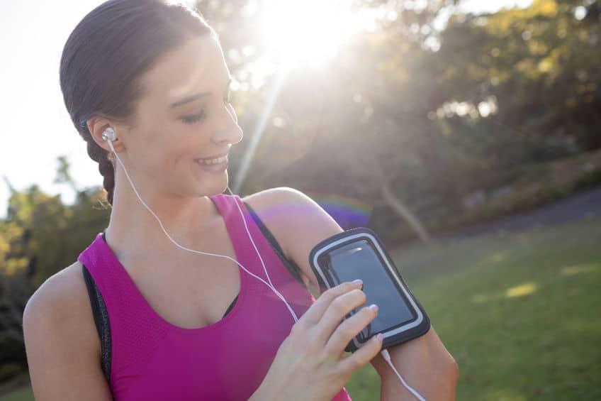 Mulher com braçadeira para celular e fone de ouvido no parque