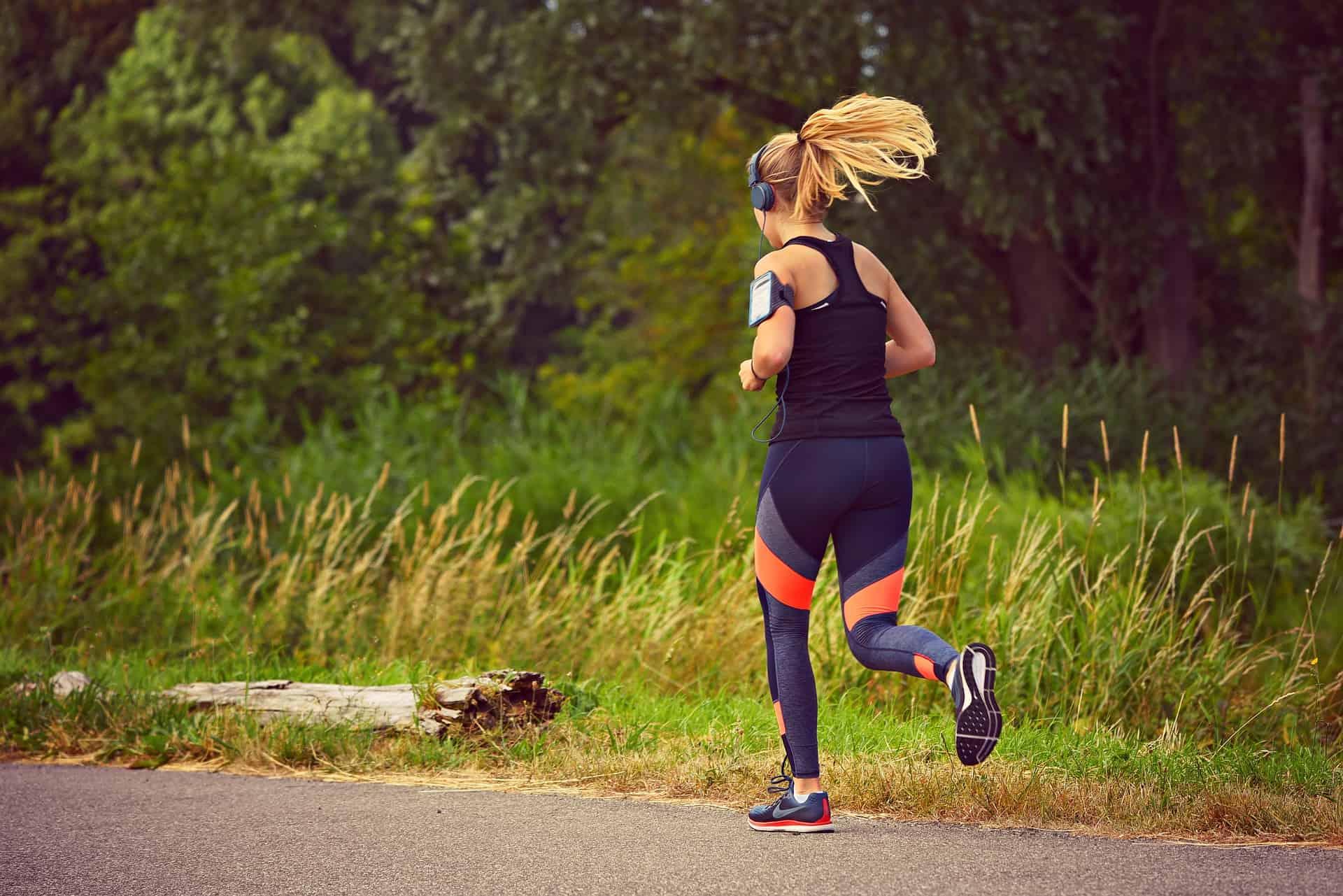 Mulher correndo no parque, com braçadeira para celular no braço e fone de ouvido.