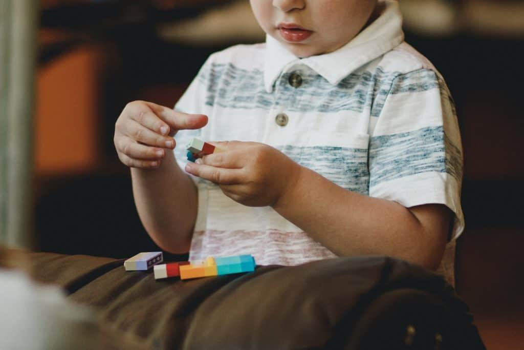 Imagem de uma criança pequena brincando com Lego