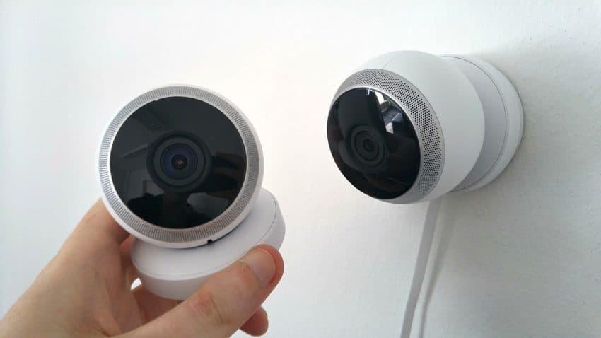 Imagem mostra uma pessoa segurando uma câmera de segurança, enquanto outra câmera de segurança está grudada na parede.