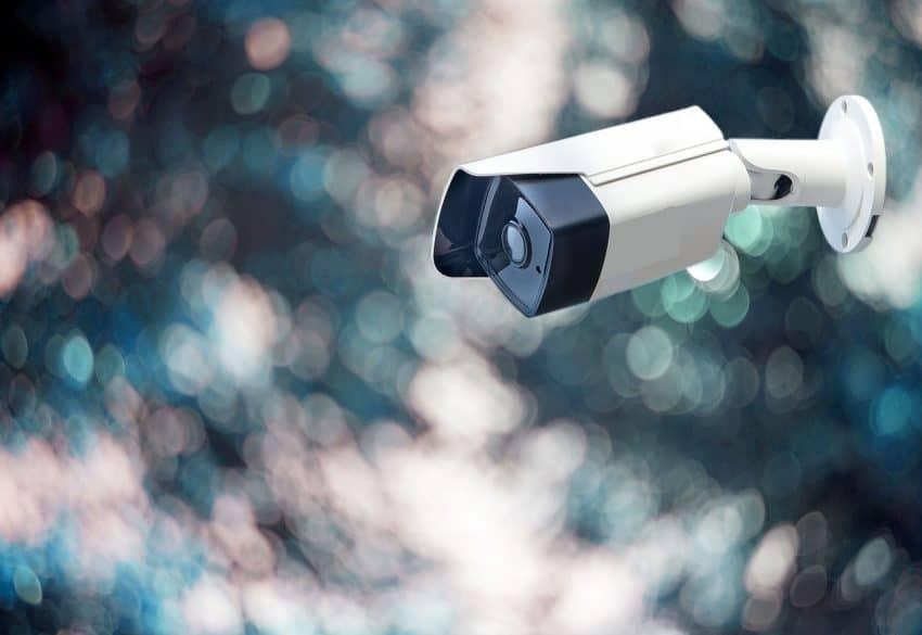 Imagem mostra câmera de segurança contra um fundo abstrato.