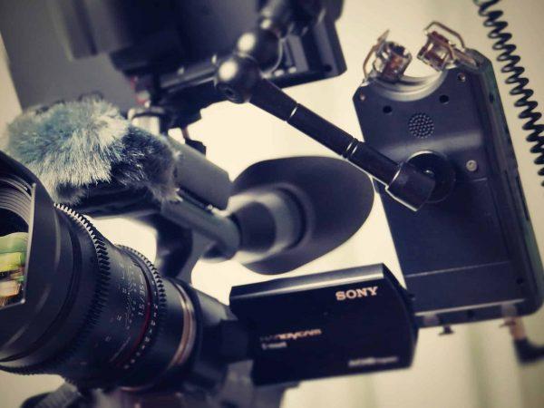 Imagem mostra uma câmera filmadora profissional com um microfone acoplado.