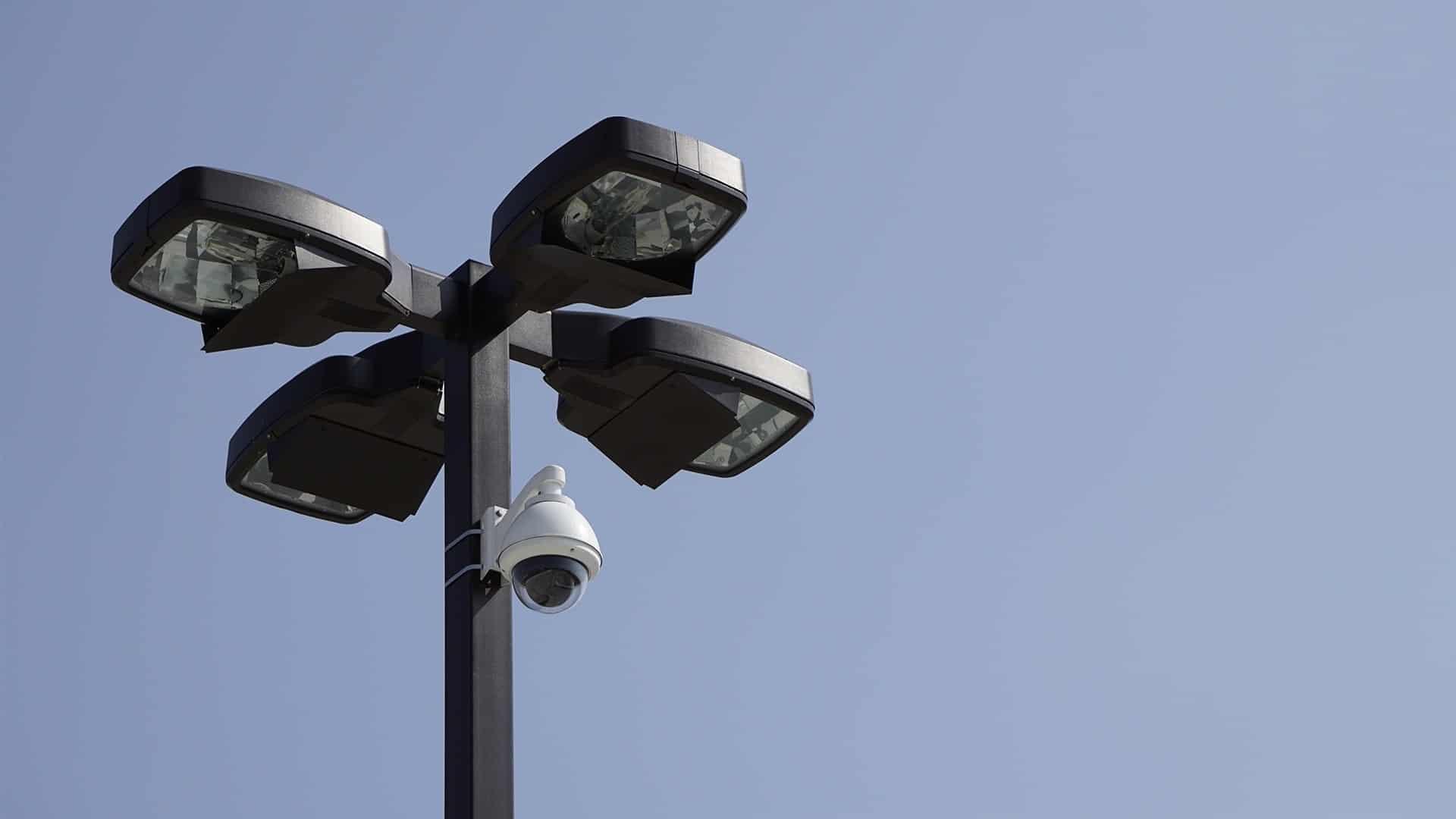 Imagem mostra uma câmera de vigilância em um poste de iluminação.