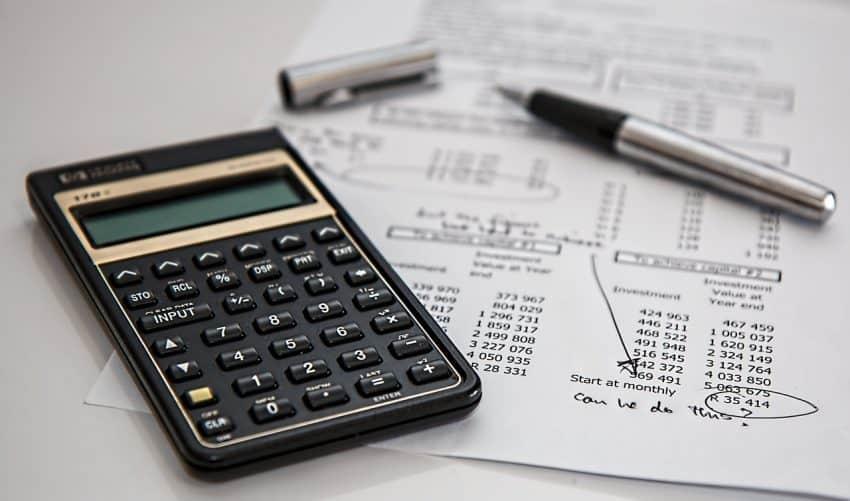 Imagem mostra uma calculadora e uma caneta ao lado em cima de um documento.