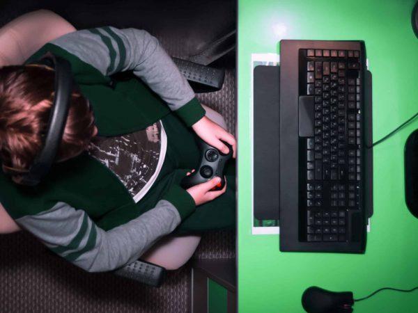 Garoto jogando em frente ao computador sentando em uma cadeira confortável.