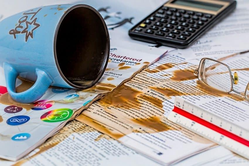 Caneca derramando café sobre folhas de trabalho impressas, com objetos ao fundo.