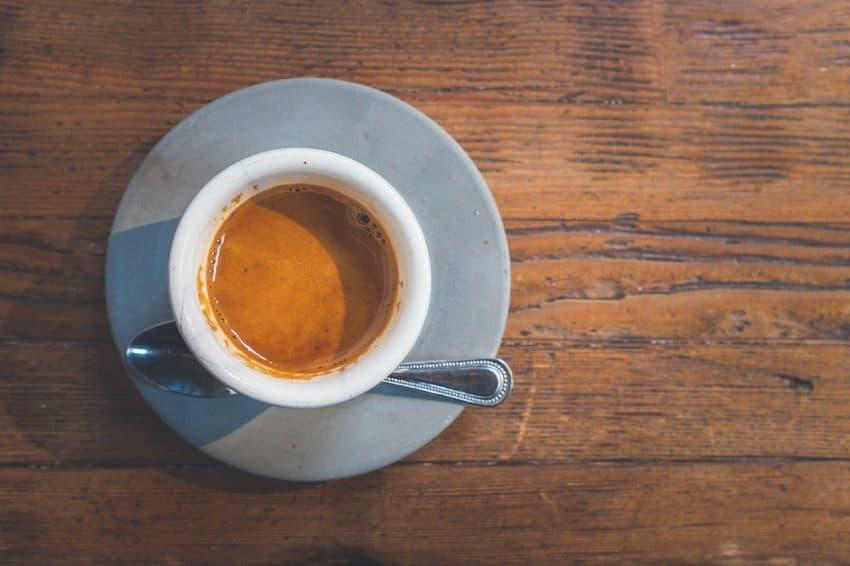 Café expresso encorpado visto de cima no pires com colher ao lado.