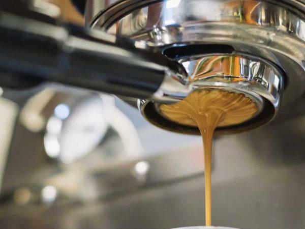 Café encorpado saindo do bico da máquina de café expresso.