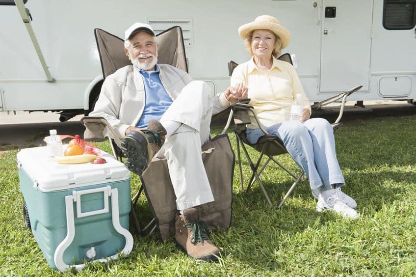 Casal mais velho sentado em frente a trailer de camping com caixa térmica ao lado.