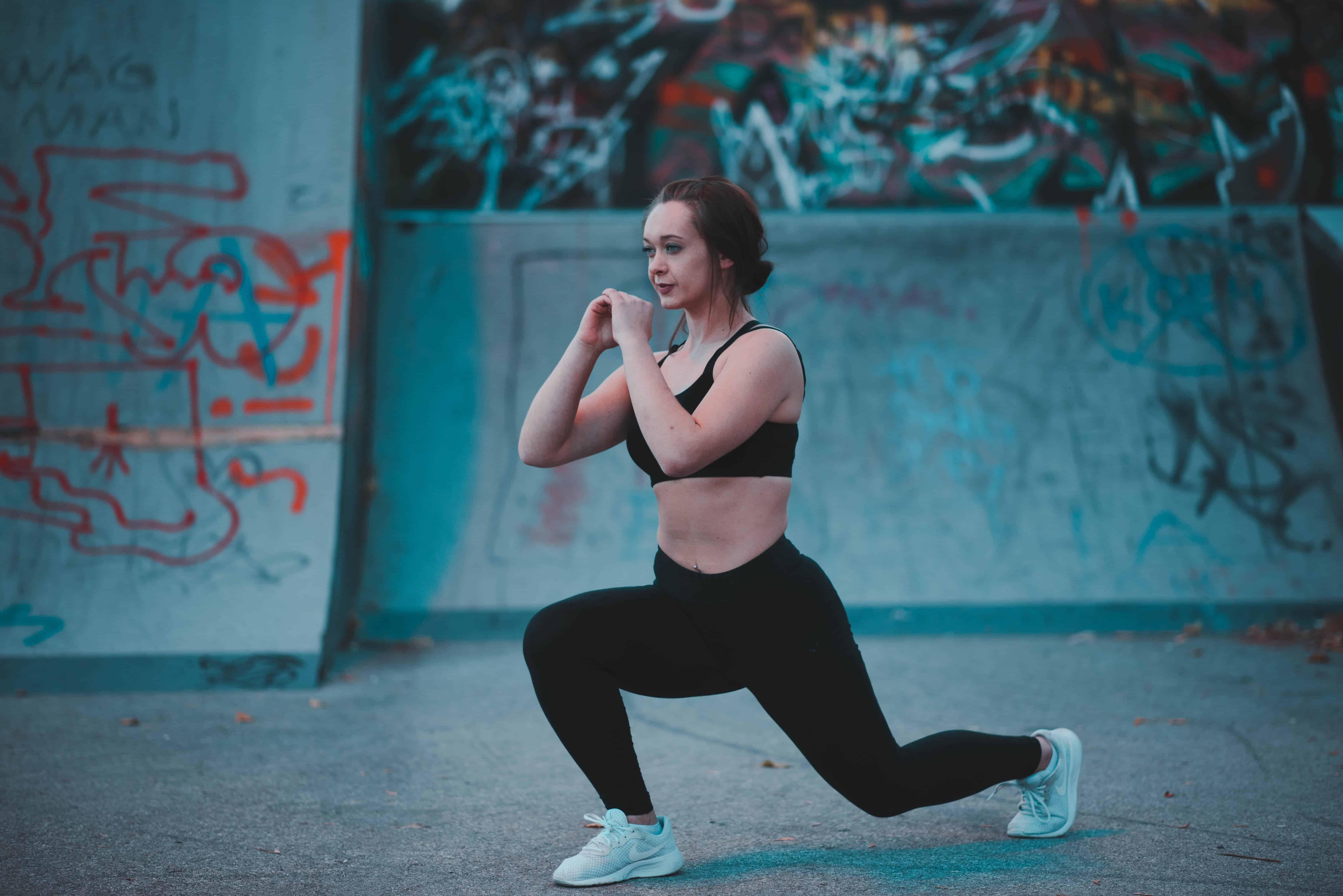 """Foto de uma mulher de legging preta e top preto, praticando o exercício """"afundo"""", próximo a uma parede grafitada."""
