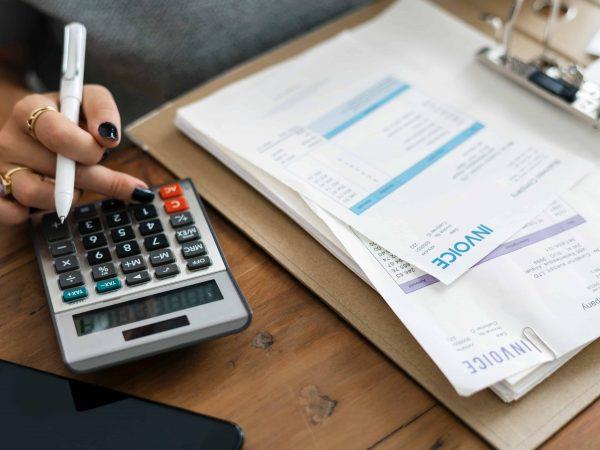 Imagem mostra uma mulher segurando uma caneta enquanto utiliza a calculadora.