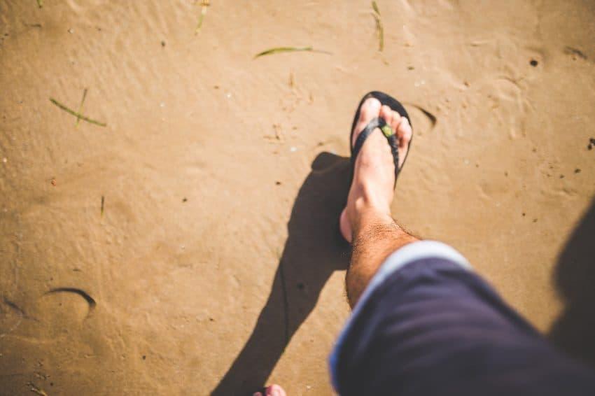 Imagem destaca o pé de um homem calçando chinelo enquanto caminha pela areia da praia.