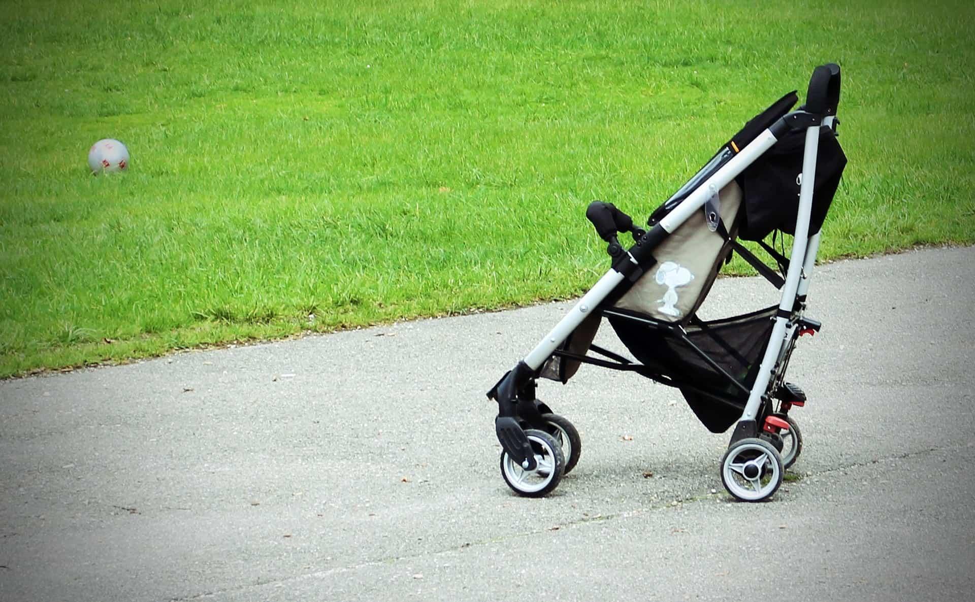 Imagem de um carrinho de bebê perto do gramado.
