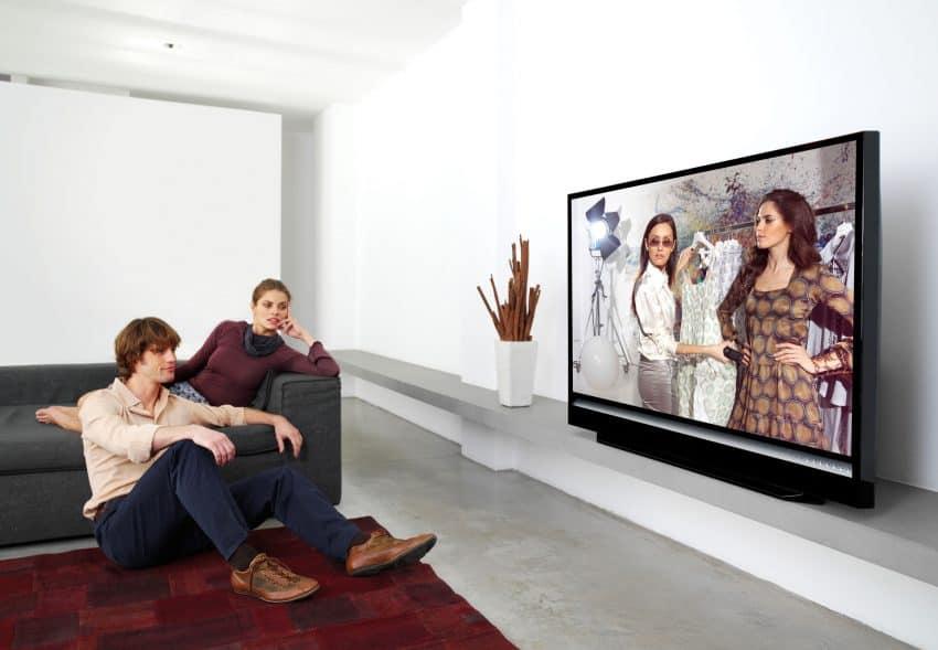 Casal sentado na sala vendo televisão, homem está sentado no chão e mulher está relaxada no sofá.