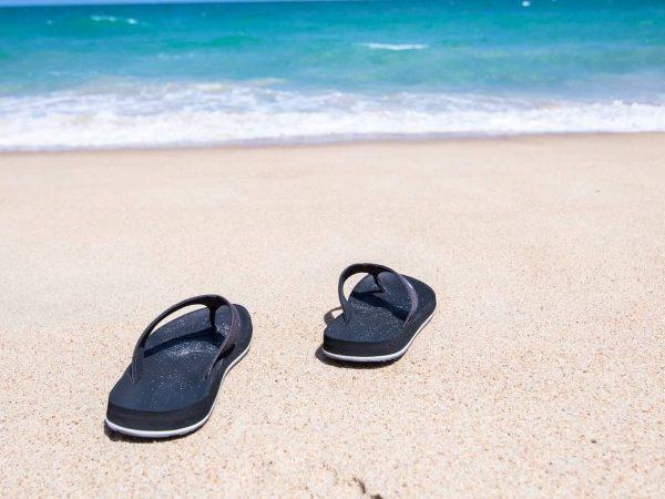 Imagem mostra uma praia, o mar ao fundo, no primeiro plano a areia e um par de chinelos sobre ela.