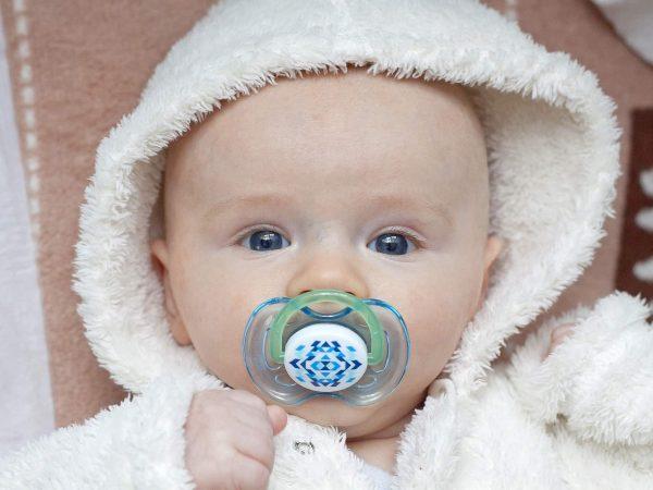 Na imagem está um bebê enrolado em um roupão com uma chupeta azul na boca.