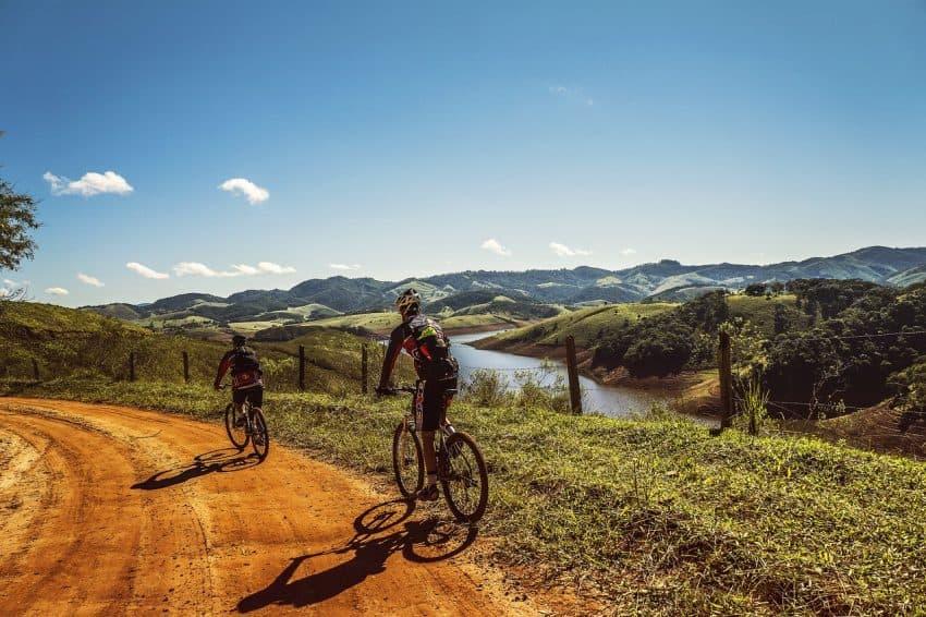 Dois ciclistas pedalando em uma paisagem com estrada de terra, rio e montanhas.