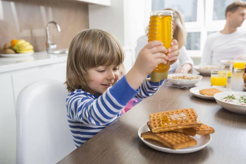 menina colocou syrup em prato de waffle
