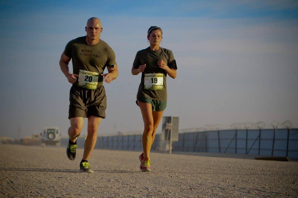 Homem e mulher correndo juntos com roupa de competição. Ela usa no braço a braçadeira para celular e fones de ouvido.