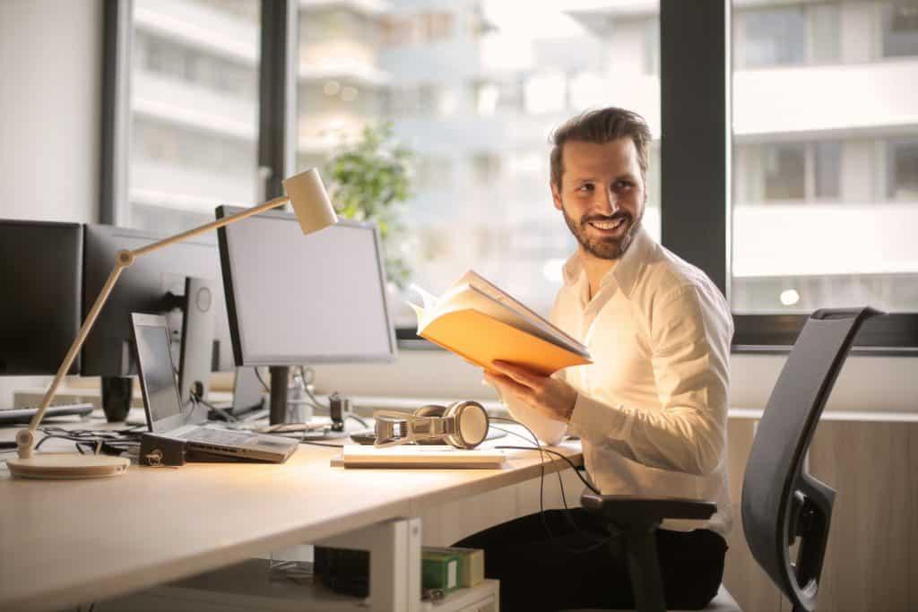 Rapaz com caderno na mão sorri sentado em frente a estação de trabalho com desktop e notebook em cima de uma base com regulagem de altura