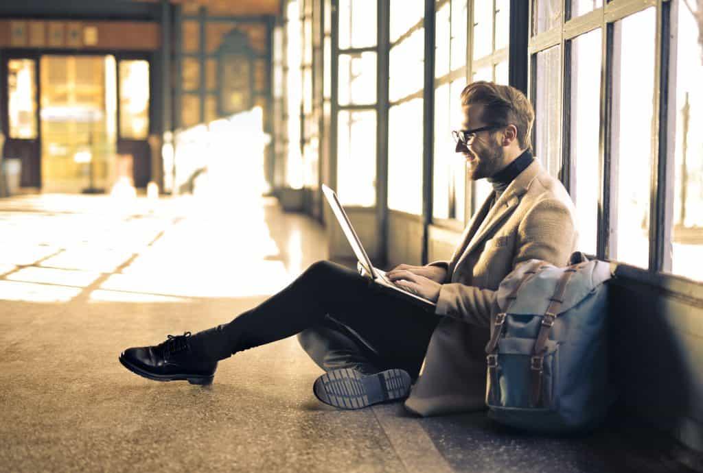 Foto de um homem sentado no chão de um espaço fechado, porém com muitas janelas, com um computador em seu colo e uma mochila ao seu lado.