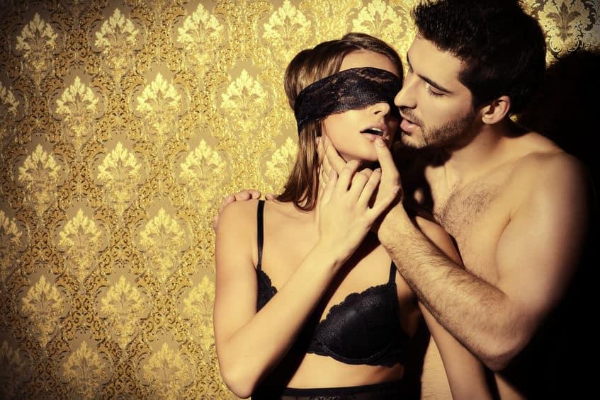 homem sem camisa por trás de uma mulher vendada, segurando o rosto dela de um jeito sensual