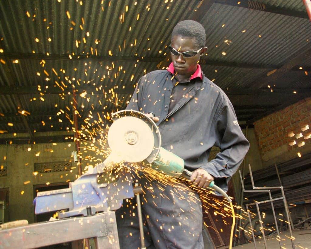 Um homem com óculos de proteção trabalhando com uma esmerilhadeira em um ferro
