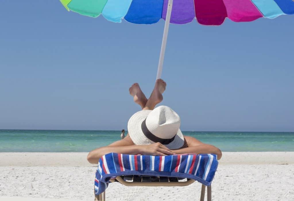 Imagem mostra uma pessoa deitada de bruços sob um guarda-sol colorido vestindo um chapéu branco