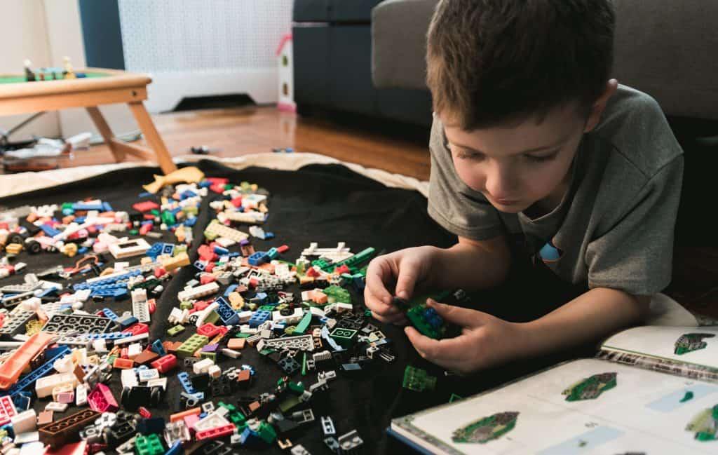 Imagem de um menino brincando com Lego