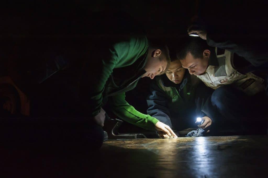 Três homens analisando o acabamento de uma mesa de madeira