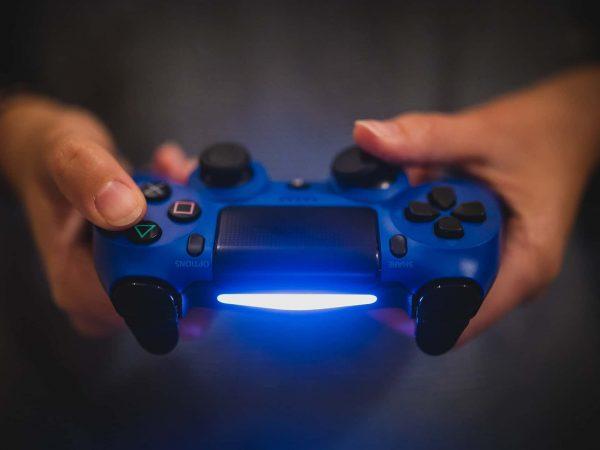 Imagem mostra, com zoom nas mãos, uma pessoa segurando um controle para PS4 azul.