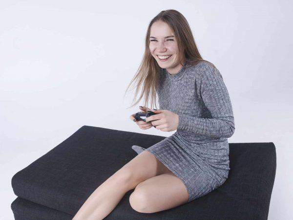 Garota sorrindo com controle de Xbox one na mão em fundo branco.
