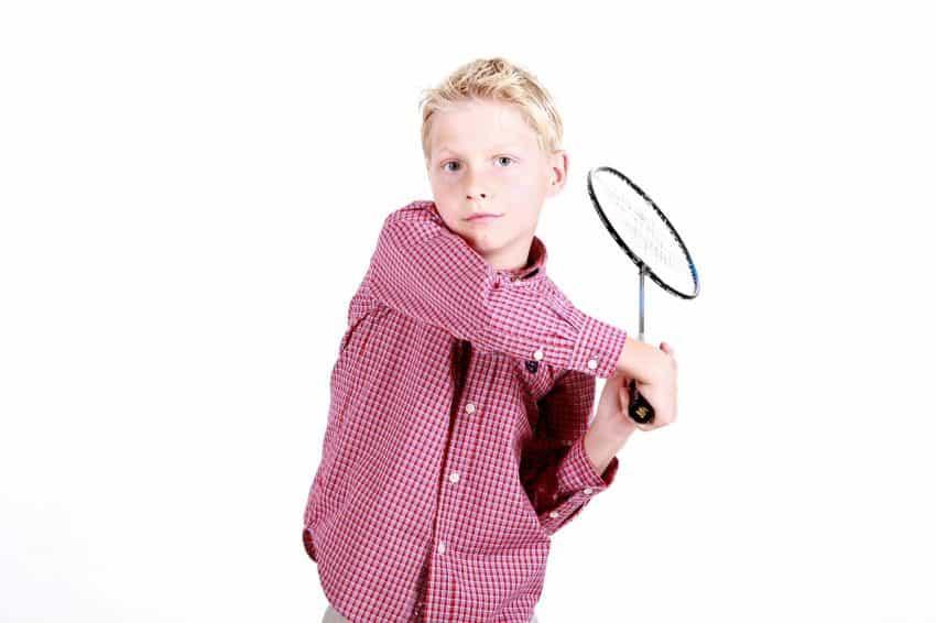 Menino segura raquete de badminton em fundo branco.