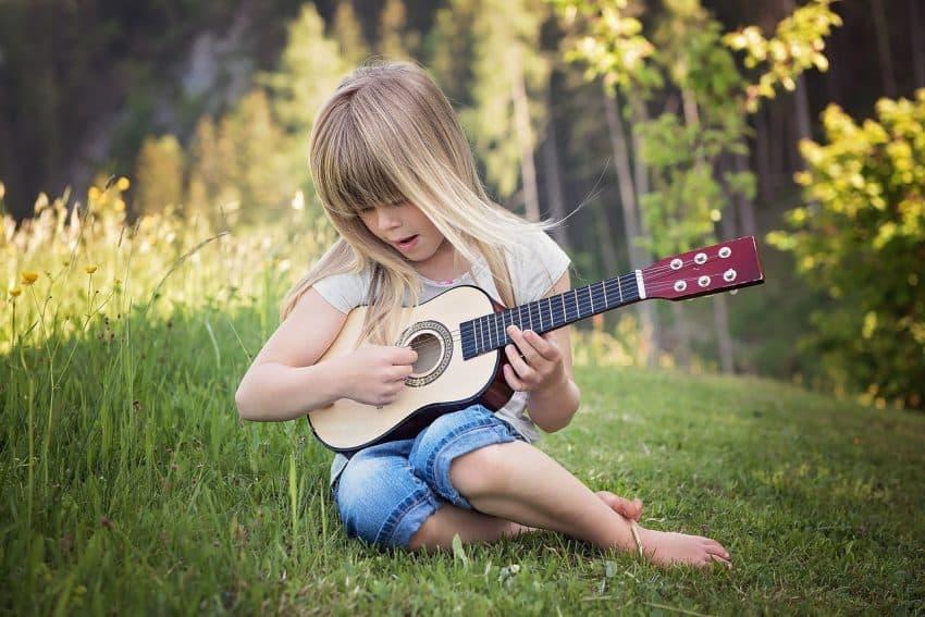 Foto de uma criança tocando um violão de tamanho compatível.
