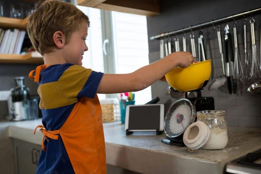 Criança pesando ingrediente em uma balança de cozinha.