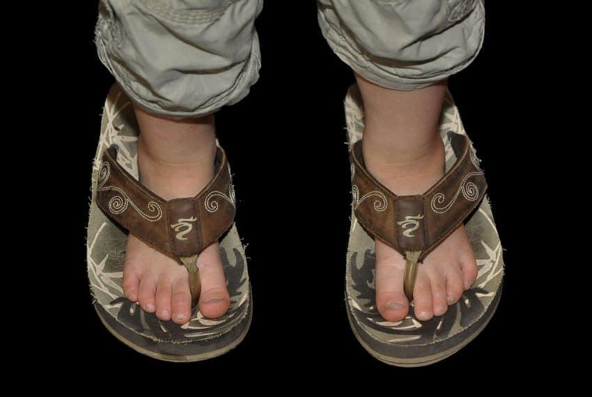 Imagem mostra os pés de uma criança em um chinelo de adulto.