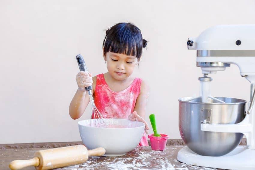 Imagem mostra criança usando batedeira.