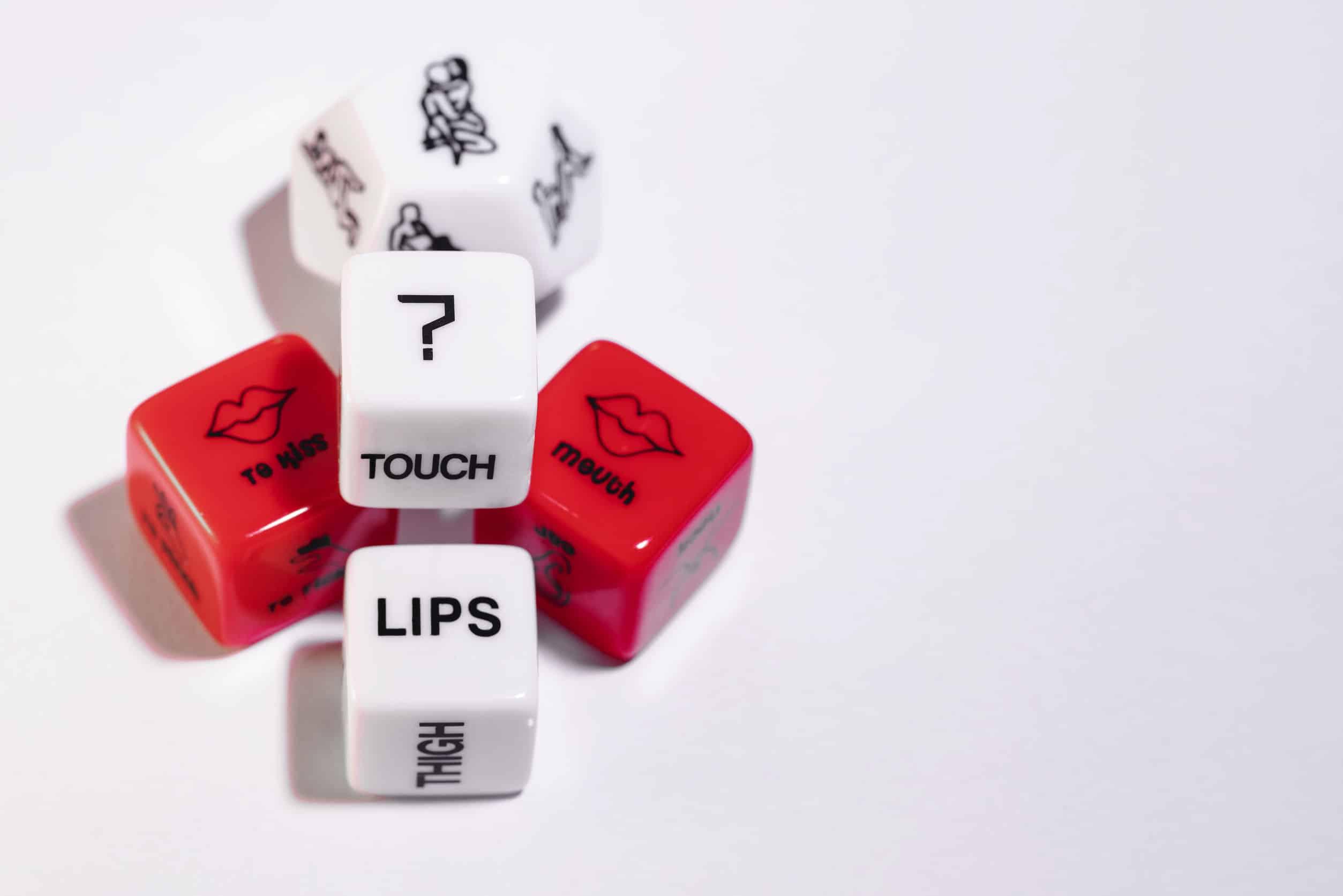 Imagem de dados eróticos brancos e vermelhos com posições, partes do corpo e ações