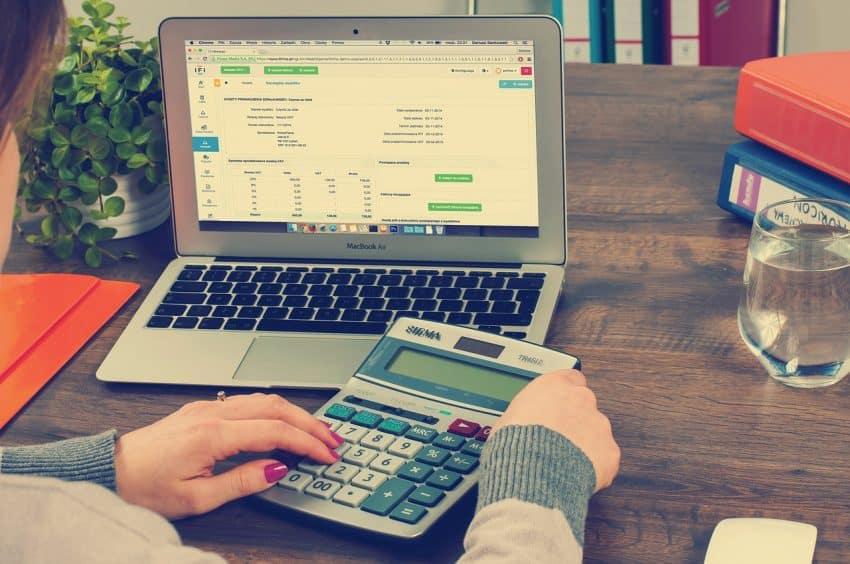 Mulher usando calculadora e um macbook em uma mesa.