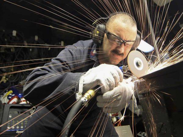 Um homem usando uma esmerilhadeira em uma mesa de metal