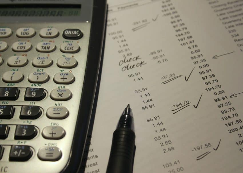 Imagem mostra uma calculadora em cima de um documento e uma caneta ao lado.