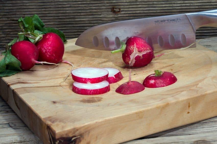 Faca santoku cortando rabanetes sobre tábua de madeira.
